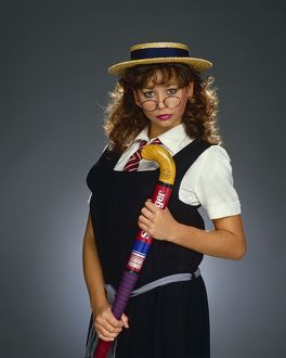 Maria Whittaker, dressed as schoolgirl, holding a hockey stick