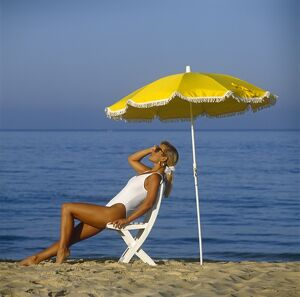 Generic shot of beautiful female on the beach with yellow umbrella