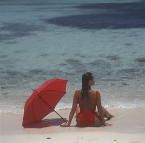 Girl sitting on the beach with red umbrella