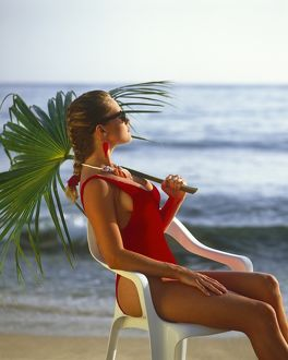 Girl in red swim suit, seated holding palm leaf